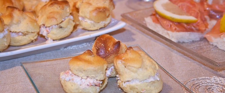 finger food buffet: crab beignets and smoked salmon canapes on glass and white dish