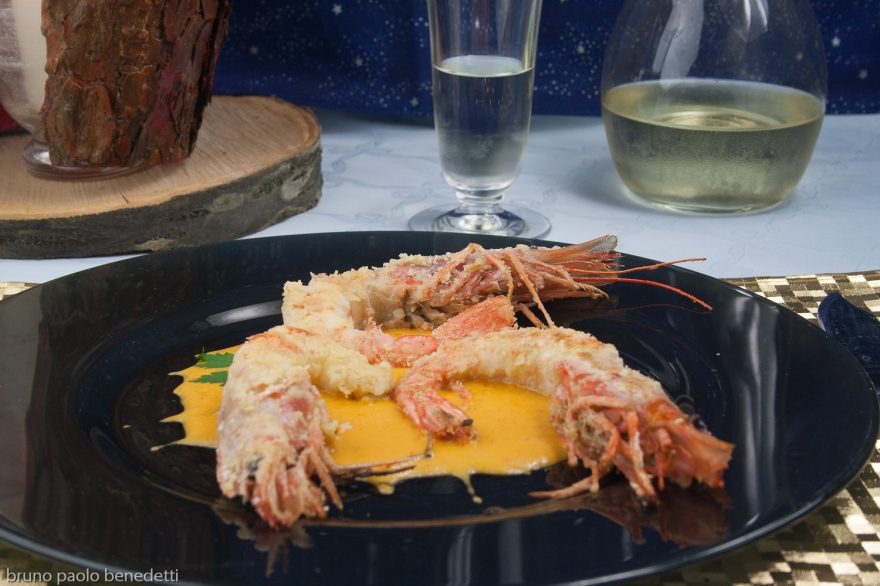 prawns on black dish with yellow pepper sauce